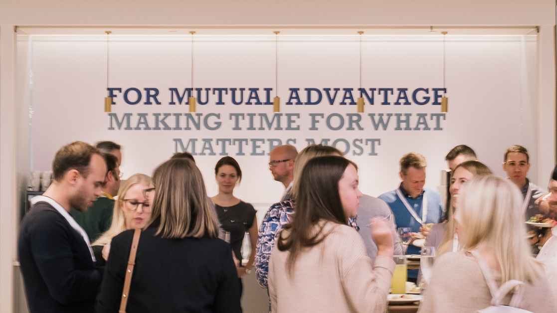 "Employees socializing by a ""for mutual advantage"" sign at a Liberty Specialty Markets event"